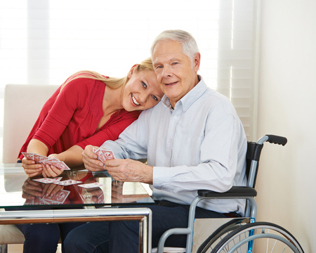 social work aged care: Happy granddaughter playing cards with grandfather in wheelchair Stock Photo