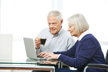 man using computer: Senior couple with laptop computer doing online shopping in internet