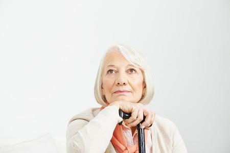 Oude vrouw met een stok omhoog kijkt peinzend