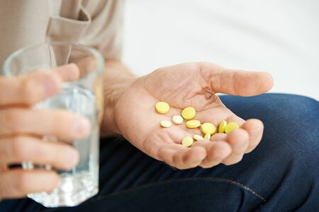 taking pill: Hand of senior man with many pills and a glass of water