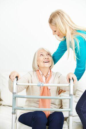 levantandose: Cuidador ayuda a la mujer de edad con andador levantarse de un sofá en casa