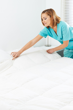 nurses: Criada que hace las camas y cambiar las sábanas en un hogar de ancianos Foto de archivo