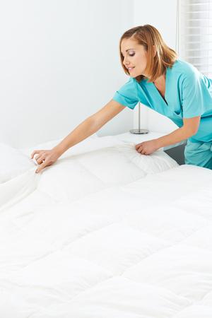 pielęgniarki: Maid Making łóżka i zmienia pościel w domu opieki