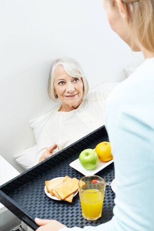 house call: Caregiver bringing breakfast to senior woman in bed