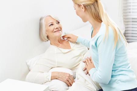 mujeres felices: Mujer joven que ayuda a la mujer mayor con su higiene personal Foto de archivo