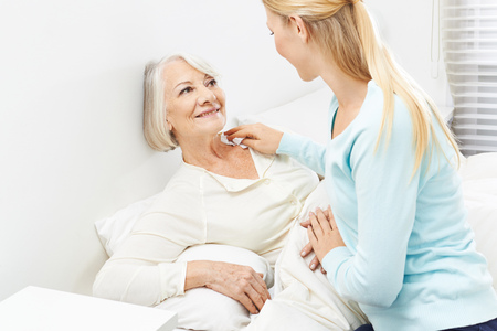 elderly patient: Young woman helping senior woman with her personal hygiene