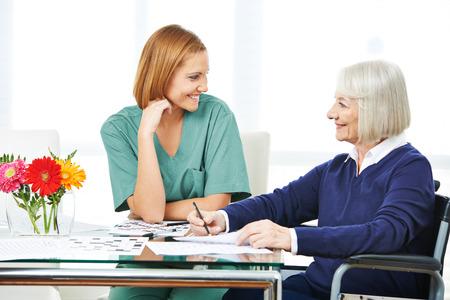 Die lächelnde ältere Frau, die Kreuzworträtsel löst, verwirrt nahe bei Krankenschwester im Pflegeheim