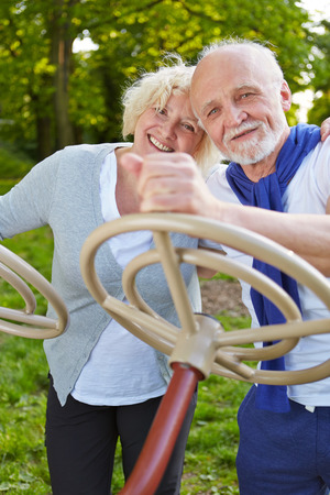 parks: Two happy senior people playing with a steering wheel in a park in summer Stock Photo