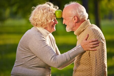 elderly woman: Happy senior caouple balancing apple between forehead in a garden