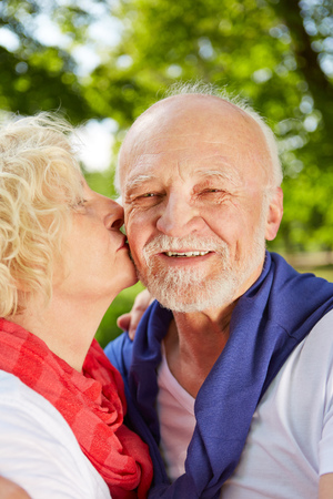 old man happy: Happy woman kissing old man on the cheek in a summer garden