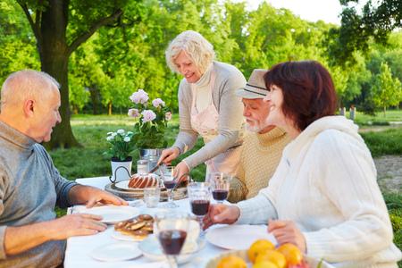 damas antiguas: Familia con gente mayor que come la torta en la fiesta de cumplea�os en un jard�n Foto de archivo