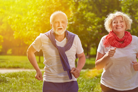 vital: Two active happy seniors running in nature in summer