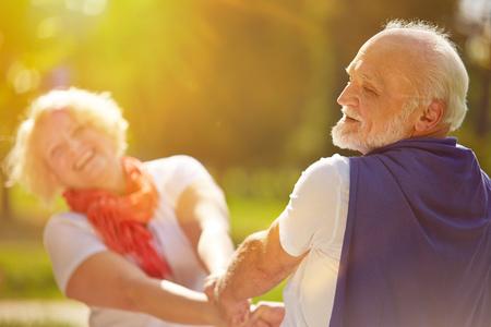 vecchiaia: Felice coppia senior ballare sotto il sole in estate in natura
