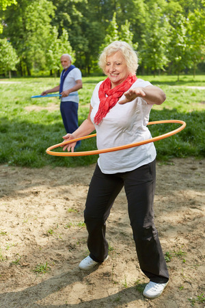 Two happy senior people using hoops in a park for a fitness training