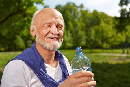 sediento: Altos hombre sediento que bebe una botella de agua en verano Foto de archivo