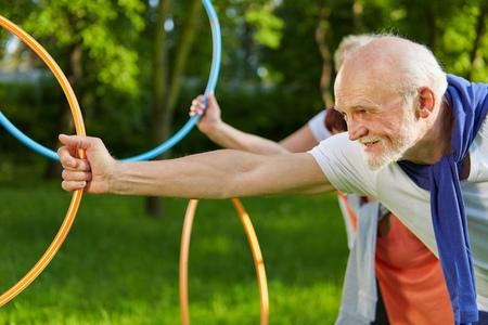 vejez feliz: Personas mayores felices que hacen deportes con aros en un jardín de verano Foto de archivo