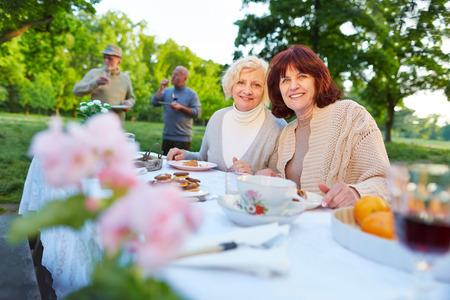 happy seniors: Smiling senior people celebrating birthday party in a summer garden