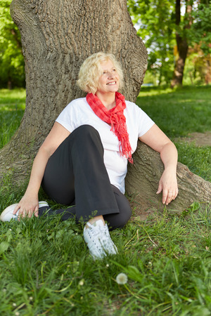 senior woman: Happy senior woman sitting at a tree in a garden in summer