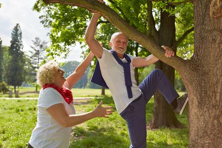 Uomo anziano arrampicata con la donna anziano su un albero in un parco d'estate