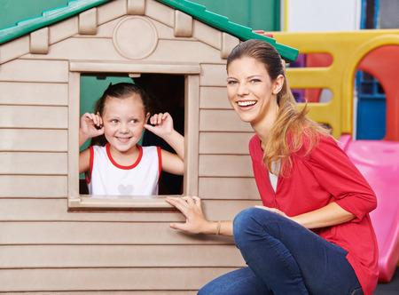 kinder: Feliz educador jugando con la niña en casa de juegos en el jardín de infantes Foto de archivo