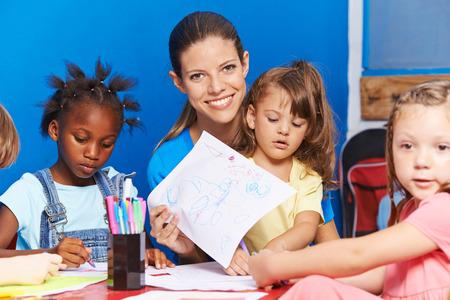 preescolar: Profesor de guardería con muchos niños que muestran un dibujo en el jardín de infantes