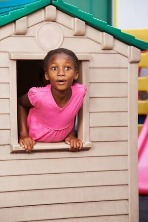 African girl looking surprised through a window in a playhouse in kindergarten