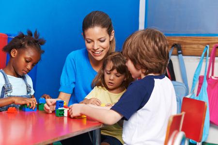 Children and nursery teacher building with blocks in kindergarten