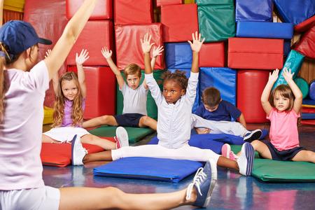 Gruppo di bambini che fanno i bambini ginnastica in palestra con maestra d'asilo