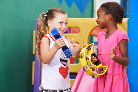 early childhood: Two girls playing music with tambourine in a kindergarten