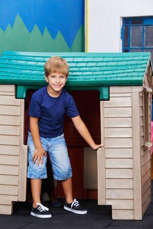 playhouse: Happy boy standing in front of playhouse in kindergarten