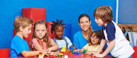 Kinder spielen mit Bauklötzen in der Kinderbetreuung mit Kindergärtnerin