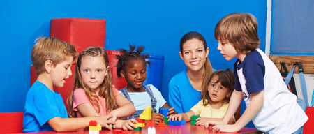 niños sentados: Niños que juegan con los ladrillos del edificio en el cuidado de niños con el maestro de guardería
