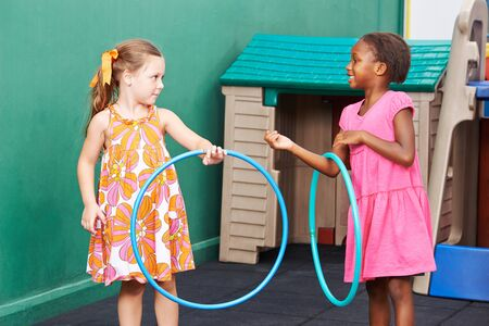 hoops: Two children playing together with hula hoops in preschool