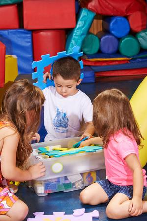 kinder: Los ni�os que limpian los juguetes en una caja en el jard�n de infantes Foto de archivo