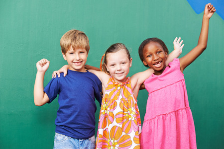 school playground: Cheering happy group of children in a kindergarten