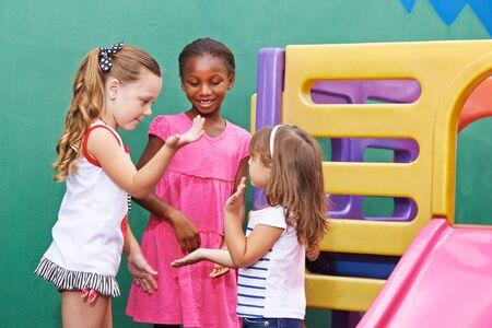 three children: Three children playing clapping game together in a kindergarten
