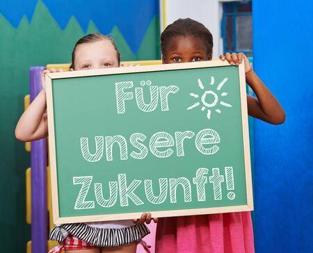 """educacion ambiental: Ni�os que sostienen la pizarra con lema alemana """"Fuer unsere Zukunft"""" (Por nuestro futuro) Foto de archivo"""