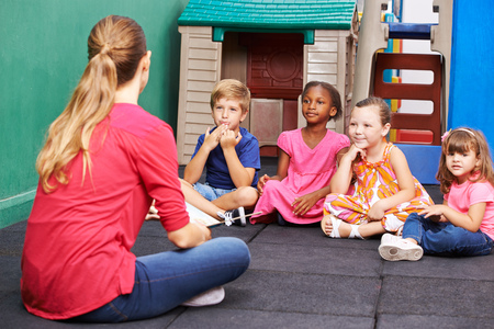 Discussion group of children in kindergarten talking to nursery teacher Stock Photo