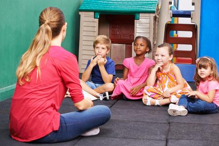Gruppo di discussione di bambini nella scuola materna a parlare con maestra d'asilo Archivio Fotografico
