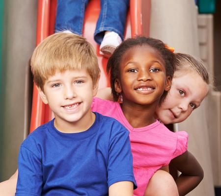 niños en recreo: Grupo de niños sentados uno detrás del otro en una diapositiva en el jardín de infantes Foto de archivo