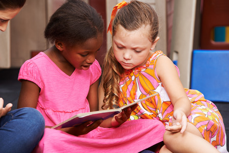 kinder: Dos muchachas que miran juntos un libro de imágenes en el jardín de infantes Foto de archivo