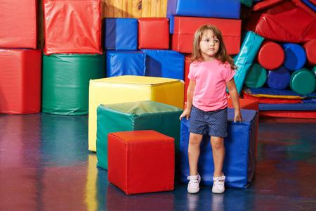 preescolar: Niño sentado solo en el gimnasio de una escuela preescolar