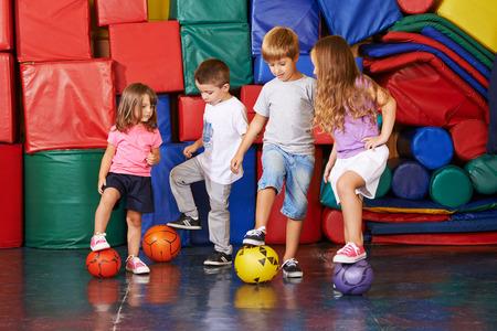 baloncesto chica: Cuatro ni�os jugando al f�tbol en el gimnasio del jard�n de ni�os juntos