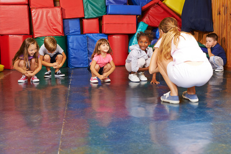 preschool teacher: Children doing gymnastics in physical education with nursery teacher in preschool