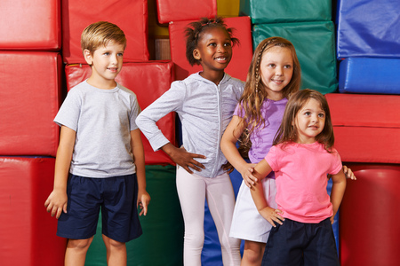 sports hall: Smiling group of children standing in gym of a elementary school