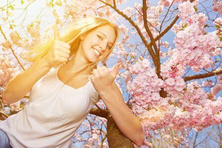arbol de cerezo: Joven mujer feliz celebración molestó sus pulgares en el árbol de la flor de cerezo