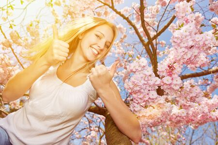 bother: Young happy woman holding bother her thumbs up at cherry tree blossom