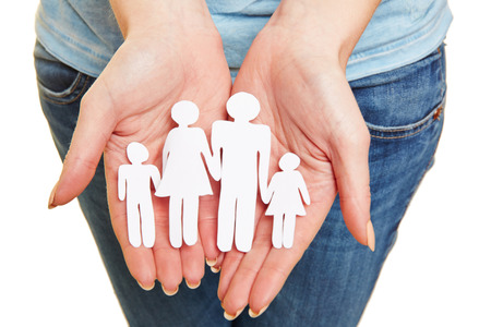 family planning: Hands holding paper family as symbol for family planning Stock Photo