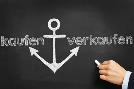 buy shares: Hand writing the German words kaufen (buy) and verkaufen (sell) on blackboard