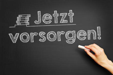 precaution: Hand writes in German Jetzt vorsorgen! (Take precaution now!) on blackboard